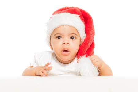 child finger: African baby in red Christmas hat looks surprised
