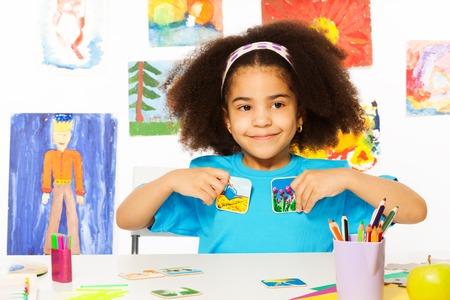 preescolar: Niña africana juega al juego del desarrollo, sostiene tarjetas