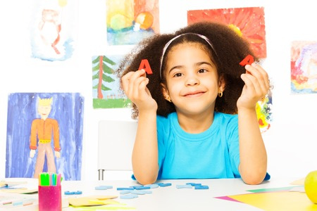 child drawing: Cute African girl show letters learning alphabet Stock Photo