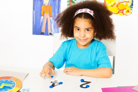 autistic: Cute African girl learn numbers with coins