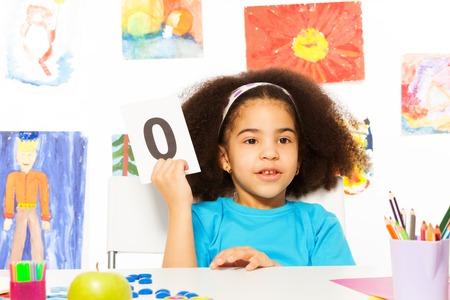 preescolar: Niña africana mantiene flashcard con cero en el escritorio