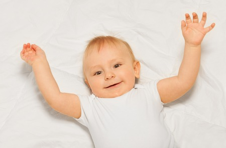 babygro: Chubby small baby with arms up on white blanket