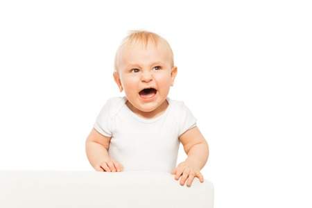 angry baby: Angry small baby with open mouth in white bodysuit Stock Photo