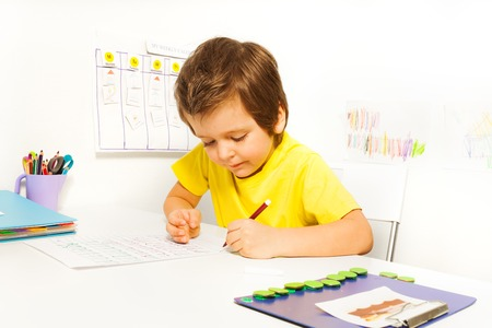 Skoncentrowany mały chłopiec pisać ołówkiem sam