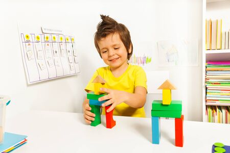 example: Cute boy putting blocks replicating example Stock Photo