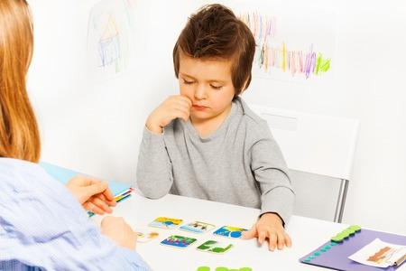 Konzentrierte Junge spielt die Entwicklung Spiel am Tisch