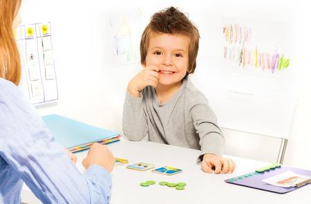 Uśmiechnięty chłopiec gra rozwijającą grę z kartami