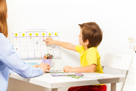 Boy points at activities on calendar learning days Standard-Bild