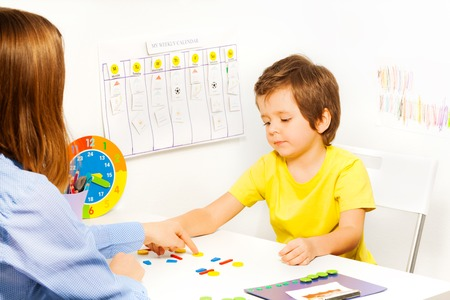 autistic: Boy putting colorful shaped coins in order Stock Photo