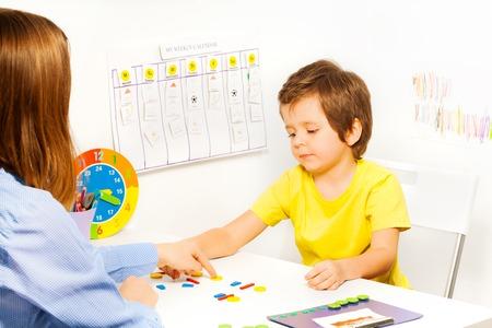Chłopiec oddanie kolorowe kształcie monety w celu