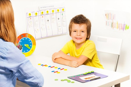 autistic: Smiling boy with colorful coins in order