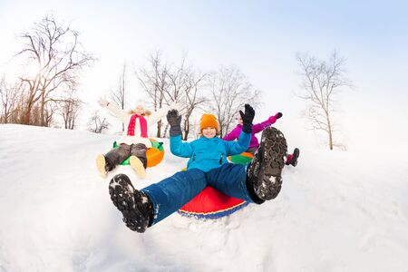 sledging people: Boy and two girls sliding down on the tubes Stock Photo