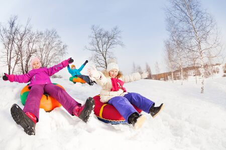 sledging people: Happy girls and boy slide on colorful tubes