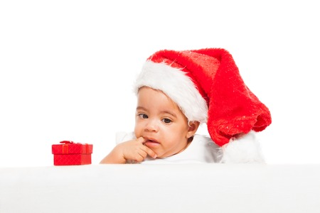 African baby paci finger wearing red Christmas hat photo