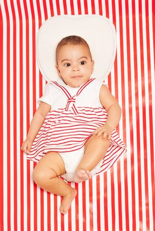 African baby in striped dress laying on blanket photo