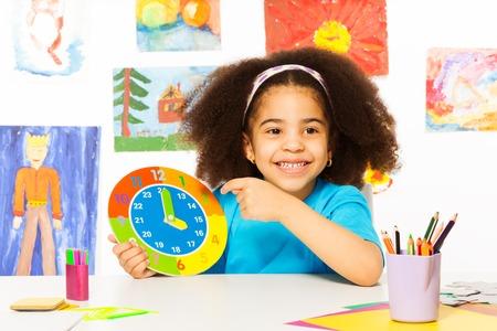 African girl holding carton clock time