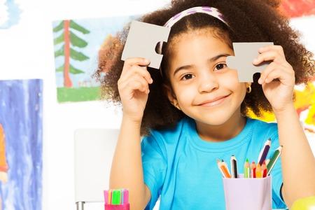 パズルのピースを保持するアフリカの女の子の肖像画 写真素材
