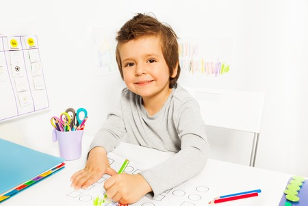early learning: Positive small boy draws with pencil during ABA