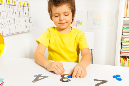 Smiling boy put coins on numbers learning count Stock fotó