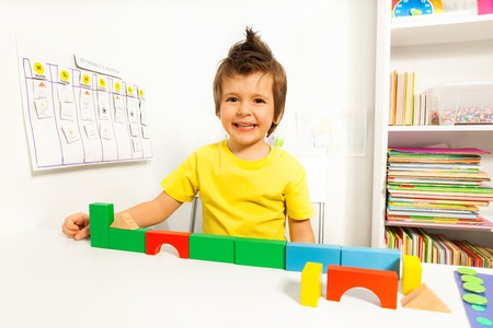 autistic: Laughing cute boy putting blocks in sequence Stock Photo