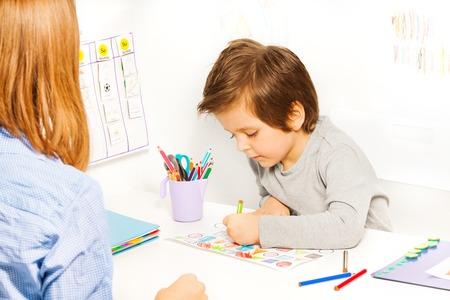 De jongen houdt potlood en kleuren de vormen op papier Stockfoto