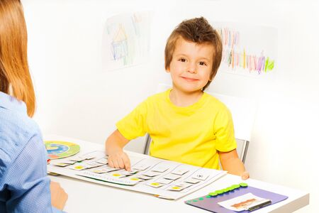autistic: Smiling boy plays in game learn days of the week