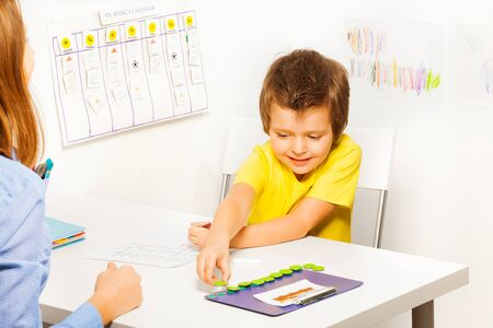 motivating: Smiling boy puts coins during developing game Stock Photo