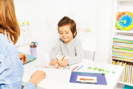 color therapy: Boy colors shapes during ABA with therapist near