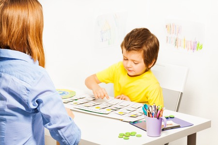 Boy plays in developing game pointing at calendar Stock Photo