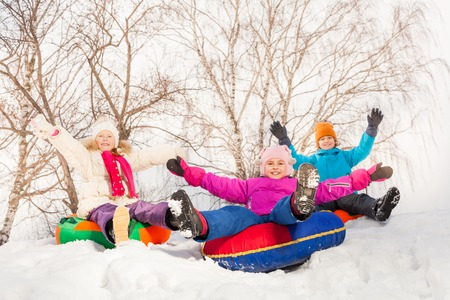 sledging people: Excited children sliding down on the tubes Stock Photo