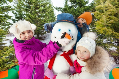 bonhomme de neige: Close-up d'enfants heureux de construire bonhomme de neige gai