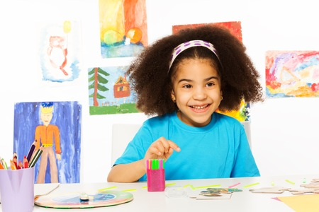 preschool classroom: Small African girl sits at the table with puzzle