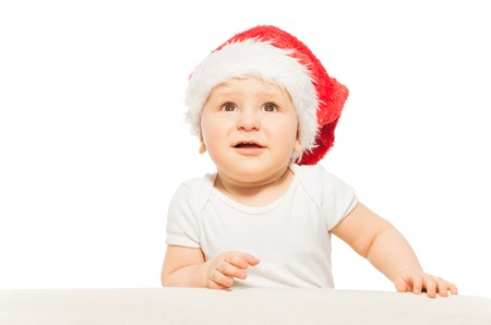 babygro: Baby in red Xmas hat looks up on white background