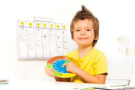 Lachende jongen die kleurrijke kartonnen klok zittend