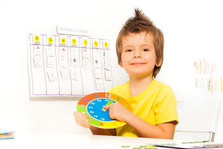 Smiling boy holding colorful carton clock sitting Stock Photo