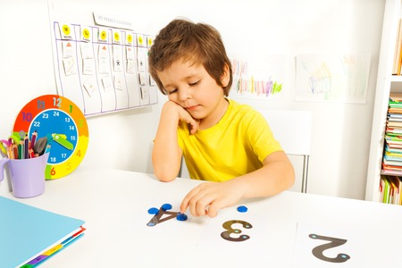 Boy puts learn to count with numbers and values Foto de archivo