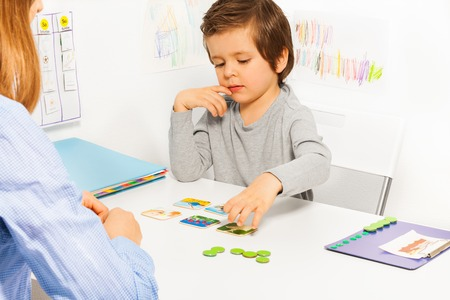 parent child: Preschooler boy and developing game with card Stock Photo