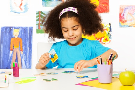 developmental: African girl putting matching cards during developmental game on table while sitting in playroom with wall behind full of children drawings
