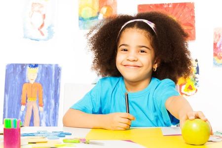 Sonriente niña africana en el escritorio sostiene un lápiz, toma la manzana mientras está sentado en la sala de juegos con una pared detrás de la cual está llena de dibujos de niños Foto de archivo