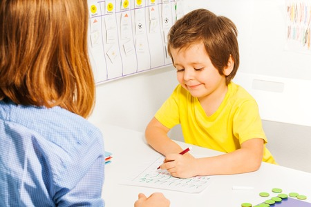 children hands: Smiling small boy in yellow T-shirt coloring the paper with pencil at the table indoors Stock Photo