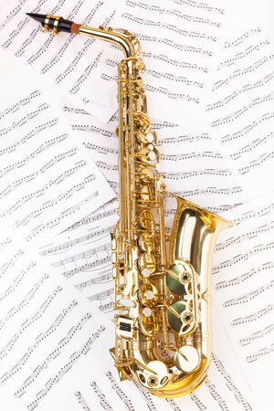 ligature: Shiny golden alto saxophone in full size on the musical notes background with standard scales exercises
