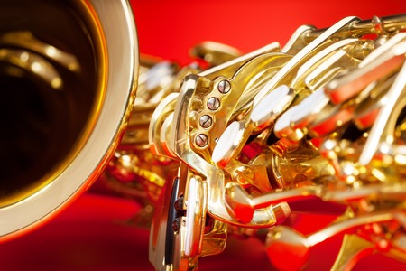 detailed view: Close-up detailed view of alto saxophone with bell and keys on the red background Stock Photo