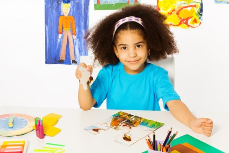 African girl puts puzzle pieces together at the table while sitting in playroom with wall behind full of children drawings Banco de Imagens