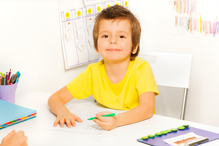 Boy drawing with pencil and learning to write during Applied Behavior Analysis ABA sitting at the table indoors Stock fotó