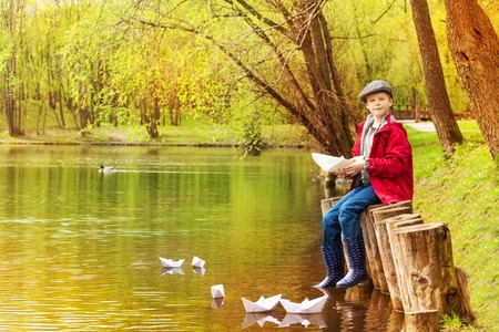 Boy sitting near the pond playing with white paper boats in beautiful forest landscape