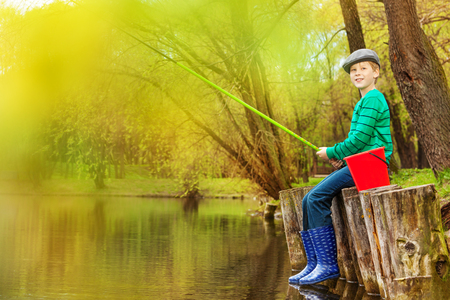 Boy fishing near beautiful pond with fishrod alone in the forest