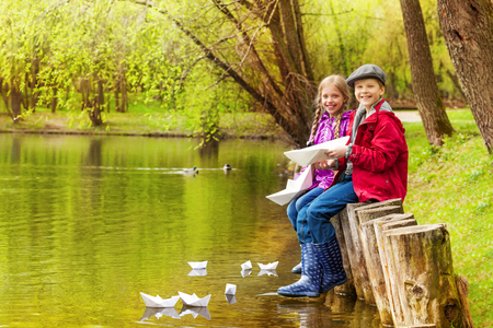 Sitting kids near beautiful pond play with paper boats with beautiful forest on background