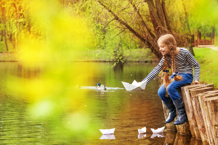 Girl sitting near the pond playing with paper boats on the water in beautiful forest landscape