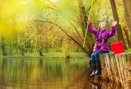 Excited happy girl holding fishrod out of the water looking at cork float with forest background