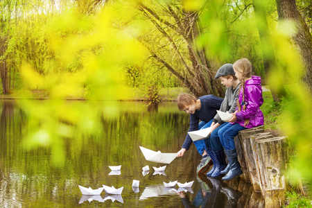 Happy three kids sitting near the pond putting paper boats on the water in beautiful forest landscape 写真素材